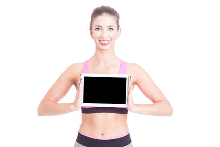 Sport female trainer holding black screen tablet and smiling isolated on white with copy advertising area Stock Photo