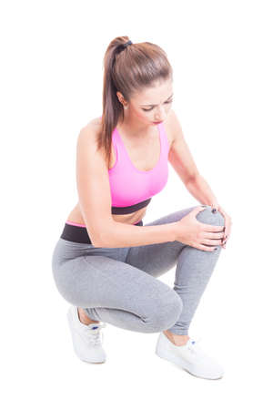 Fit girl holding her knee like being injured isolated on white background Stock Photo