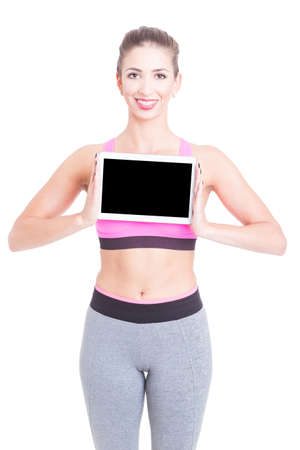 Young woman wearing aerobic clothes holding tablet gadget and smiling isolated on white with copy text space Stock Photo