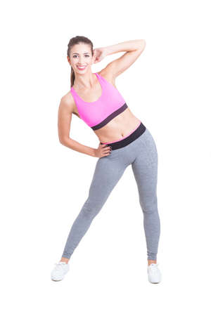 Fit attractive girl preparing for workout bending her waist isolated on white background
