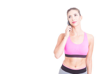 Fit girl speaking on telephone and looking up isolated on white background with copy text space