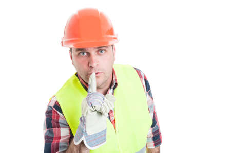 Attractive builder doing a shush gesture as quiet concept isolated on white background