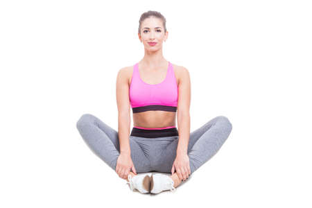 Fit lady wearing sportswear sitting and stretching her legs isolated on white background with copy text space