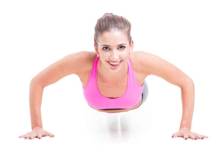 pushup: Girl working out standing in push-up position and smiling isolated on white background