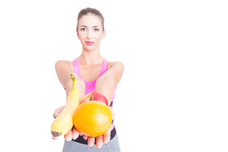 Selective focus of girl at gym holding some fruits as healthy snack isolated on white background with copy text space Stock Photo