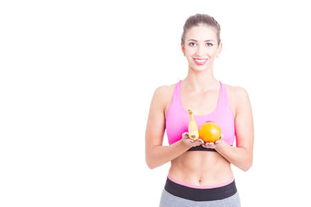 Young woman wearing sportswear at gym holding fruits as healthy diet isolated on white background with copy text space Stock Photo