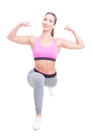 Fit girl posing in lunge position showing biceps isolated on white background Stock Photo