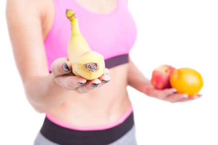 Selective focus of fit sporty girl holding banana isolated on white background