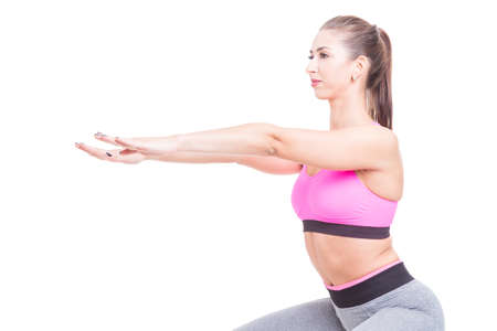 Fit lady close-up doing squats with hands up isolated on white background with copy text space Stock Photo