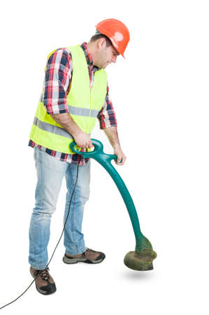 Handsome builder cutting grass with string trimmer on white copyspace
