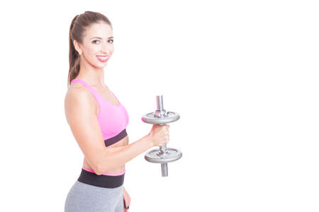 Side view of fit girl holding dumbbell with one hand and smiling isolated on white background with copy text space