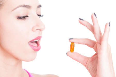 Close-up of woman taking slimming pill isolated on white background