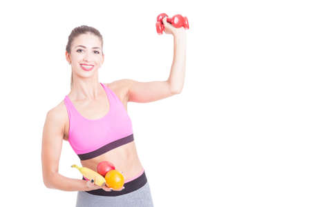 Girl holding weights and fruits in both hands isolated on white background with copy text space Stock Photo