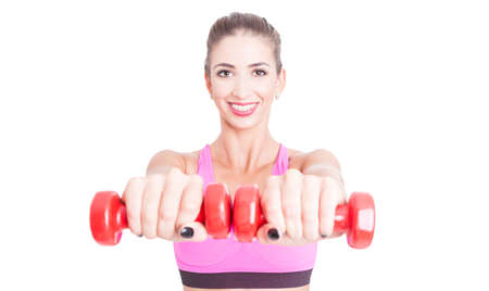 Female trainer holding up one pair of weights in selective focus isolated on white background