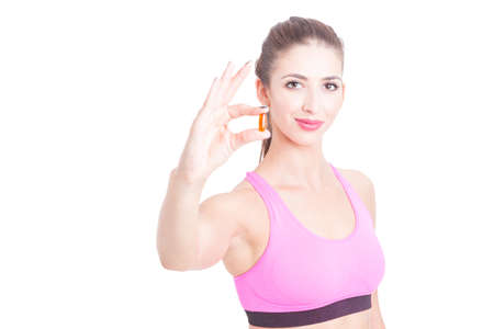 Young girl at gym showing one pills isolated on white background with copy text space