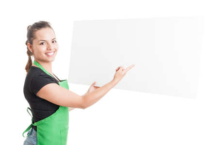 merchandiser: Cheerful beautiful seller holding and  pointing at blank cardboard with text area isolated on white background
