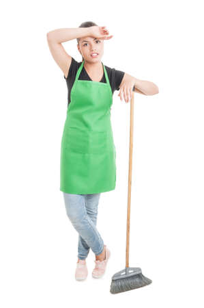 retailers: Young hypermarket employee with broom looking tired after cleaning isolated on white background Stock Photo