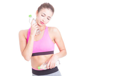 Girl at gym holding bottle of water and refreshing isolated on white background with copy text space Stock Photo
