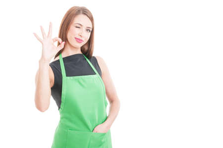 merchant: Beautiful winking employee showing ok sign isolated on white background with copy space Stock Photo