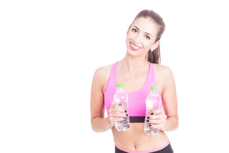Girl at gym holding bottles of water and smiling isolated on white background with copy text space