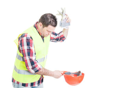Angry builder throwing his gloves into helmet as frustration concept isolated on white background with copyspace
