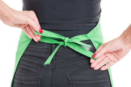 salesperson: Closeup of salesperson tying apron up behind her back isolated on white background Stock Photo