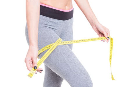 resize: Close-up of female measuring her leg with yellow tape line isolated on white background