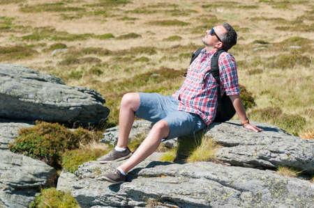 sun bathing: Male backpacker wearing shades sun bathing on top of the mountain