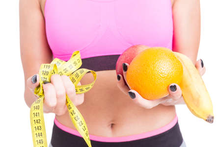 Close-up of woman at gym holding fruits and yellow tape line isolated on white background