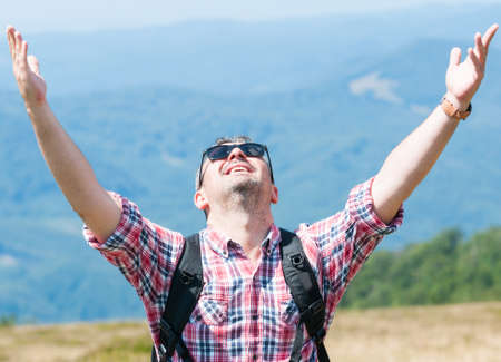 the victorious: Backpacker feeling happy and victorious on top of the mountain Stock Photo