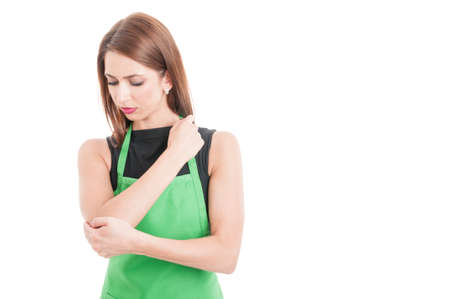 elbow pain: Pretty supermarlet seller with elbow pain isolated on white studio background with advertising area