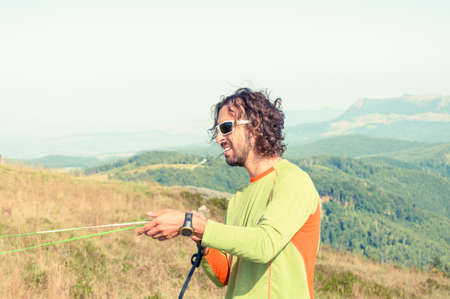 Paraglider holding ropes at landing down on sunny day with copy text space