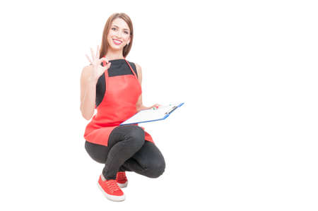 storekeeper: Joyful employee with clipboard making ok sign and smiling on white background with advertising area