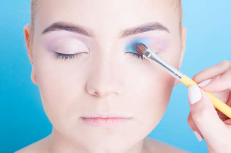 coloring lips: Close-up of applying blue eyeshadow on young womanwith brush isolated on blue background Stock Photo