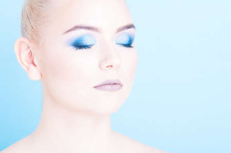 coloring lips: Close-up of beauty professional blue eyes make-up isolated on blue background Stock Photo