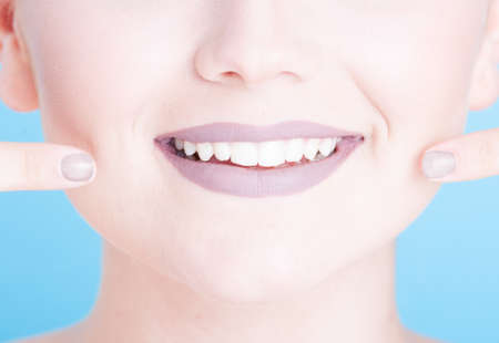 coloring lips: Close-up girl pointing her beautiful smile with lipstick isolated on blue background