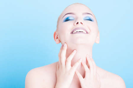 coloring lips: Girl posing with matching blue make-up and nail polish isolated on blue background with copy advertising area