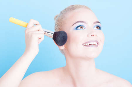 coloring lips: Beautiful girl with cool make-up holding professional brush isolated on blue background Stock Photo