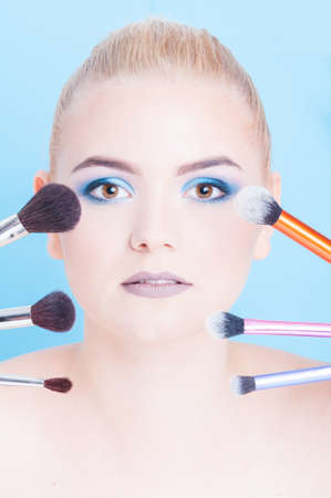 coloring lips: Portrait of beauty make-up with different kinds of brushes isolated on blue background Stock Photo