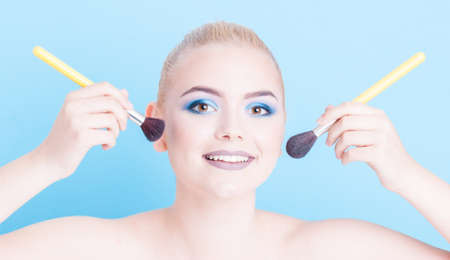 coloring lips: Girl posing as beauty professional make-up concept holding brushes  and smiling isolated on blue background