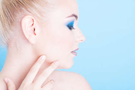 coloring lips: Side view of girl wearing matching nails and make-up isolated on blue background with copy advertising area