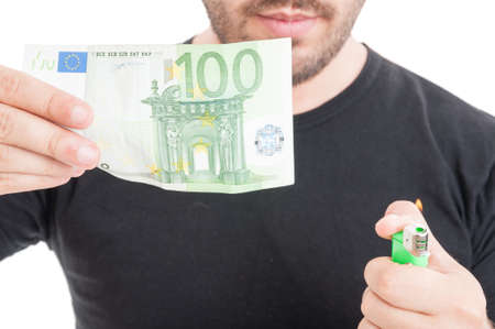 burning money: Young male burning money with lighter isolated on white background
