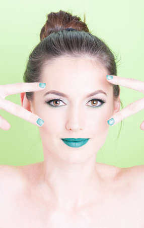 coloring lips: Girl posing with professional trendy make-up and victory gesture with matching nail polish isolated on green background Stock Photo