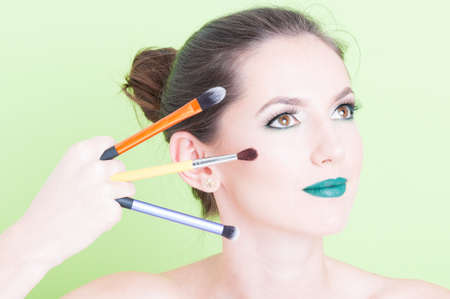 coloring lips: Girl posing with professional trendy make-up holding brushes isolated on green background with copy text space