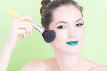 coloring lips: Portrait of woman posing with  professional brush make-up isolated on green background