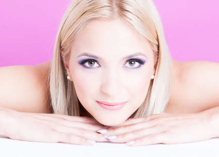 coloring lips: Blond woman posing laid down as make-up beauty concept isolated on pink background Stock Photo