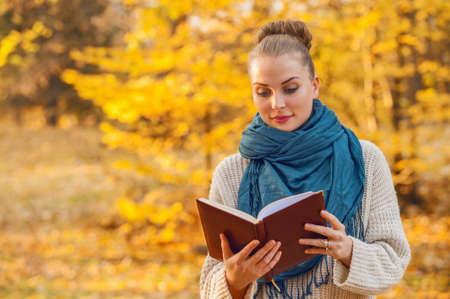enjoyment: Stylish woman relaxing in the nature while holding and reading a book with copyspace