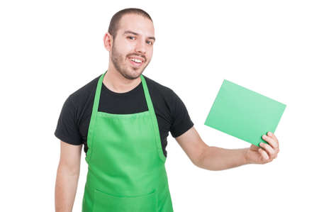 retailers: Young male market employee holding green cardboard and smiling isolated on white background with copy text space Stock Photo