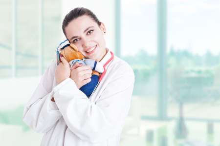Trustworthy pediatrician with stethoscope and white coat hugging plush toy with advertising area