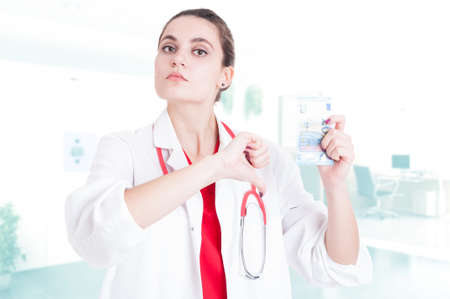 Female doctor doing disapproval gesture about medical services payment in her office